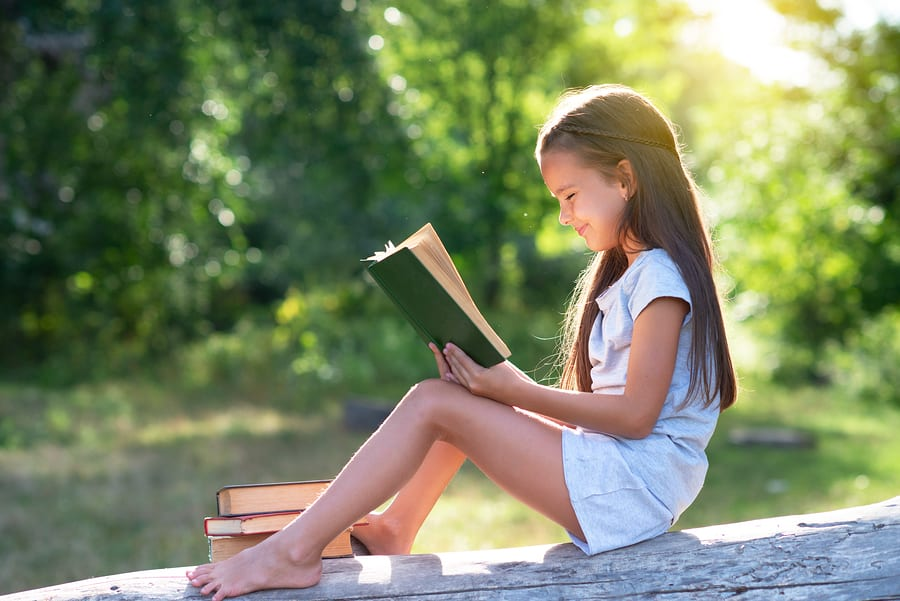 Charming little girl with long brown hair reads book outdoor sitting in park in summer; summer slide