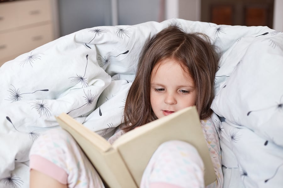 girl spending free time alone, reading attentively in her own reading nook