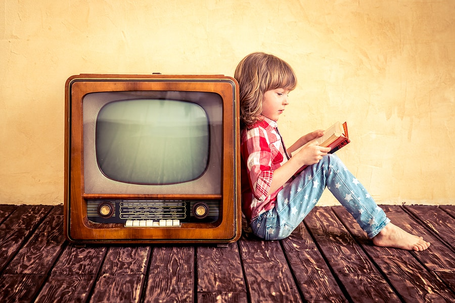 Kid reading book while leaning on retro TV. Technology, screen time