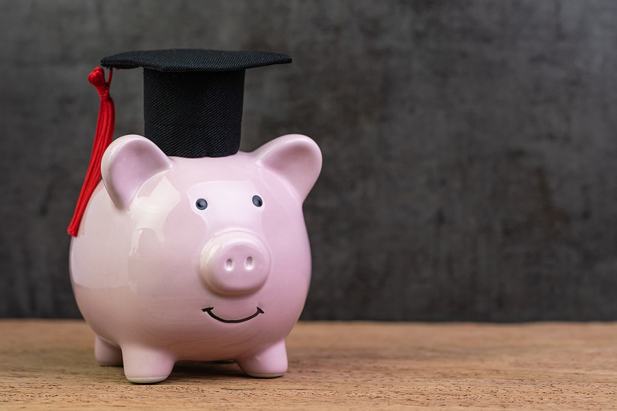 Title Funds: Smiling Pink Piggy Bank Wearing Graduated Hat On Wooden Table Wi