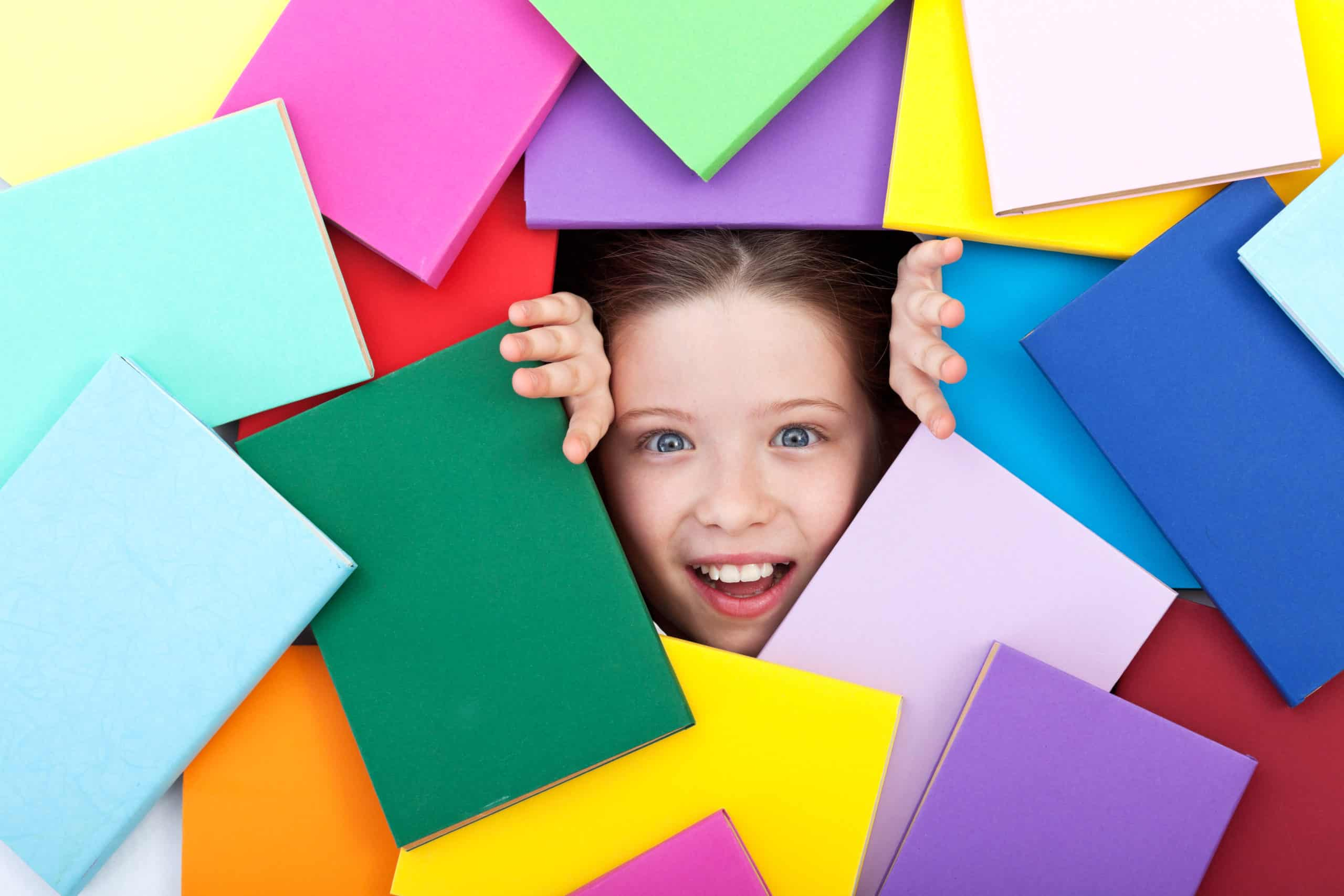 young girl emerging from beneath colorful books; kids' choices