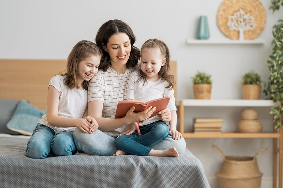 young mother reading a book to her daughters, encourage kids to read