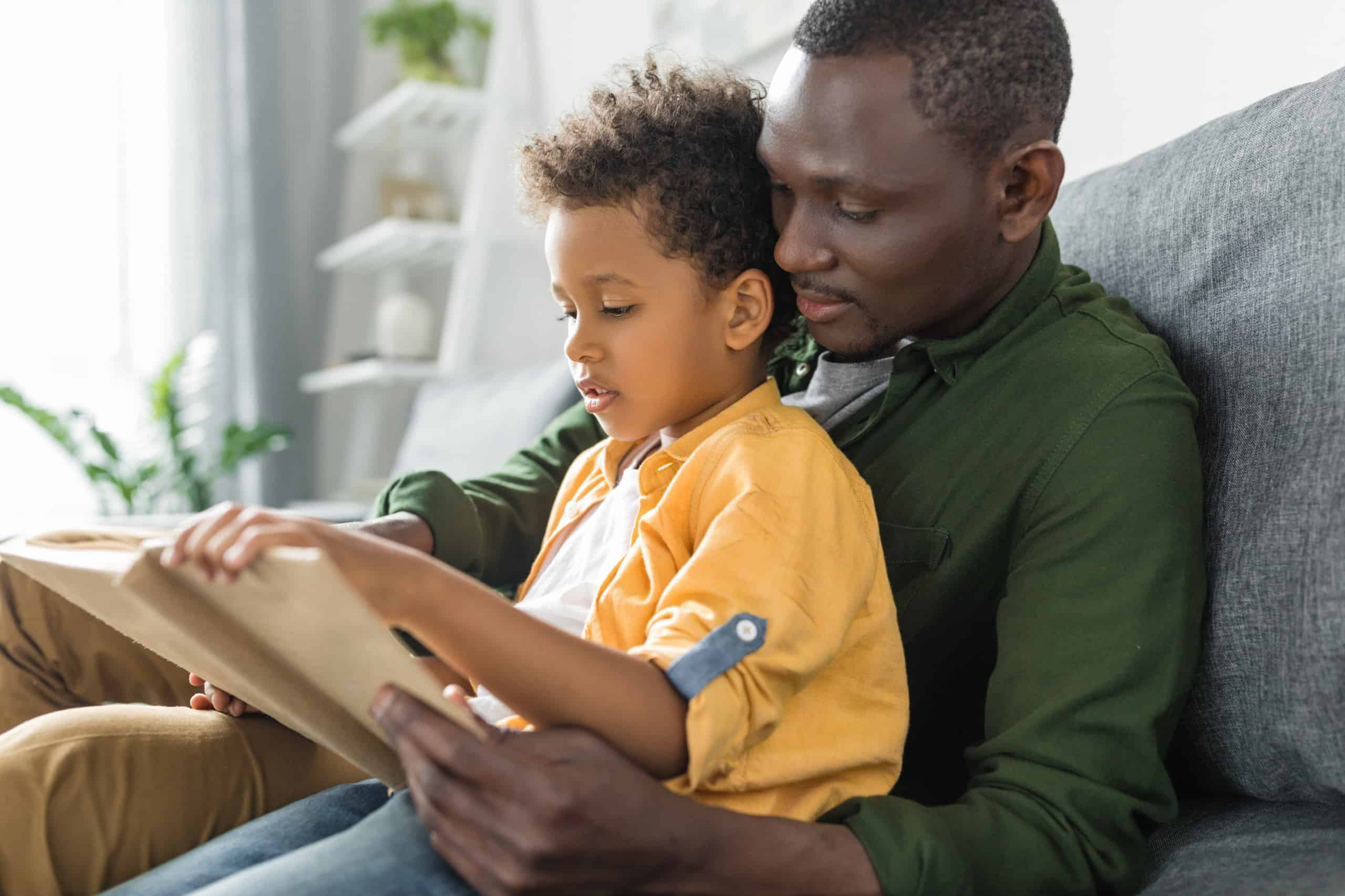 cute American father and son reading book together