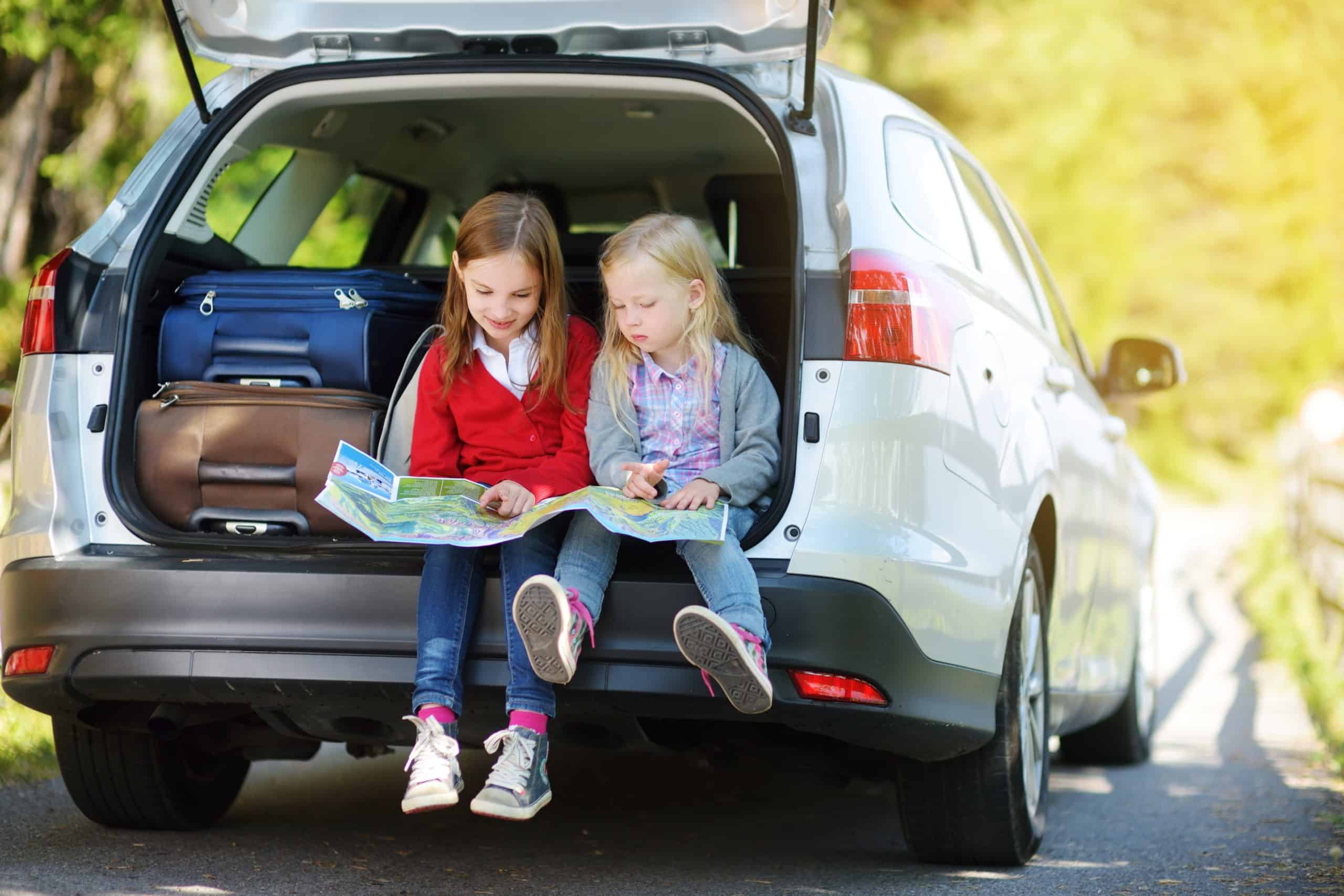 Kids reading a book in the back of a van; book titles game for road trips