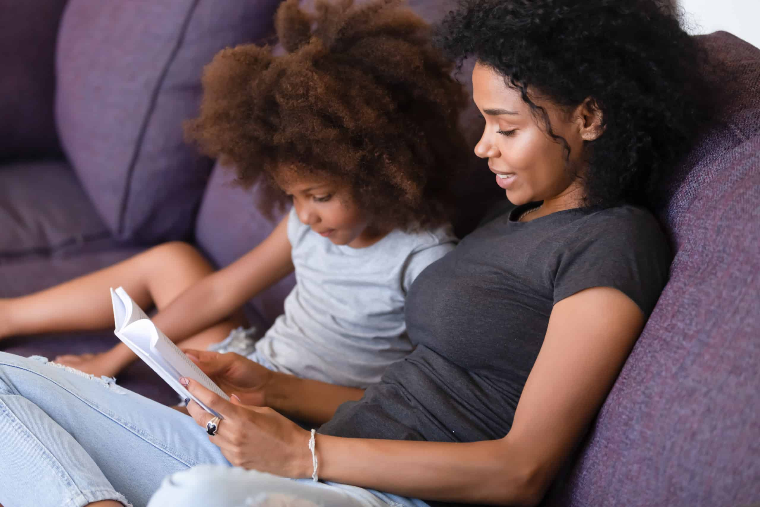 Smiling mother reading book with daughter; read with child