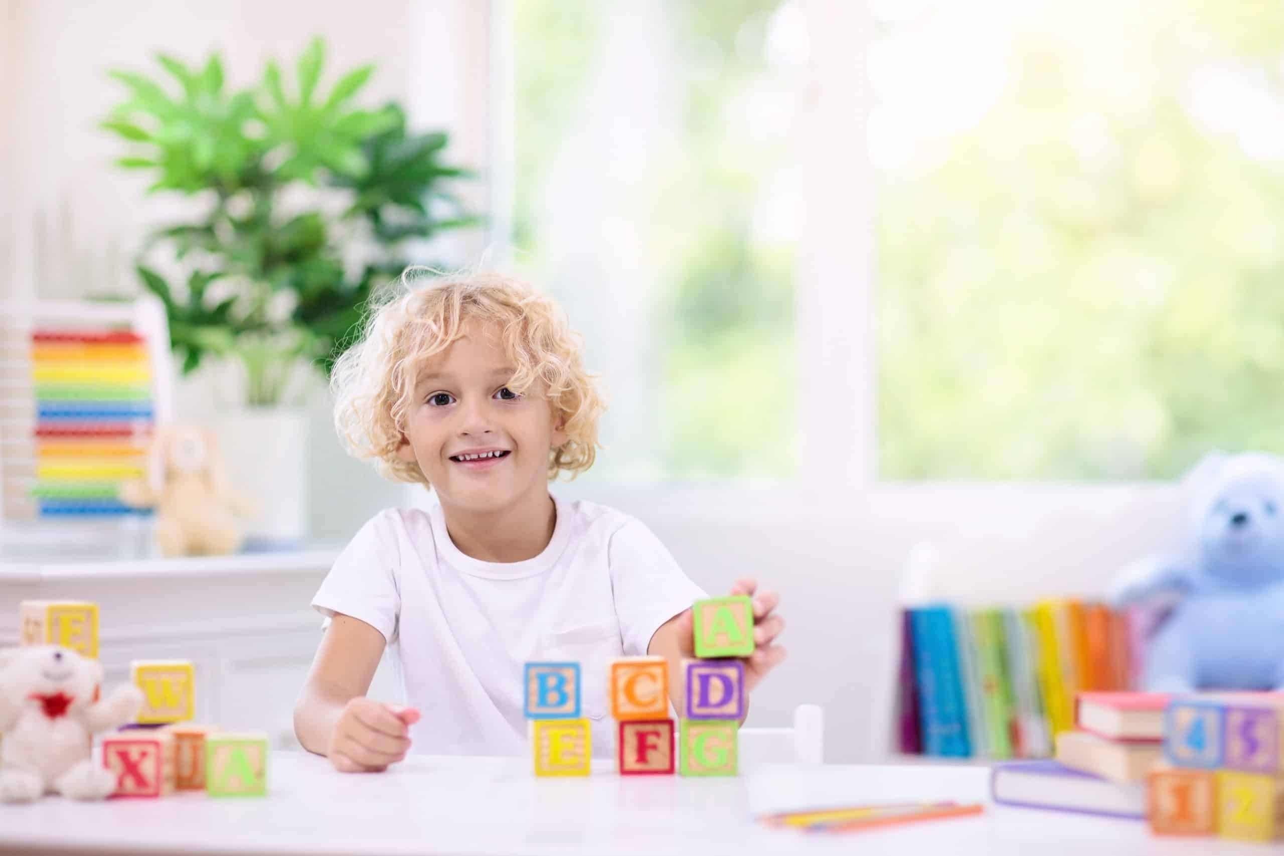 Child learning letters. Kid with wooden abc blocks; home library