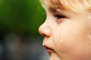 crying sad child - little girl face with tear on the cheek; normalizing emotions