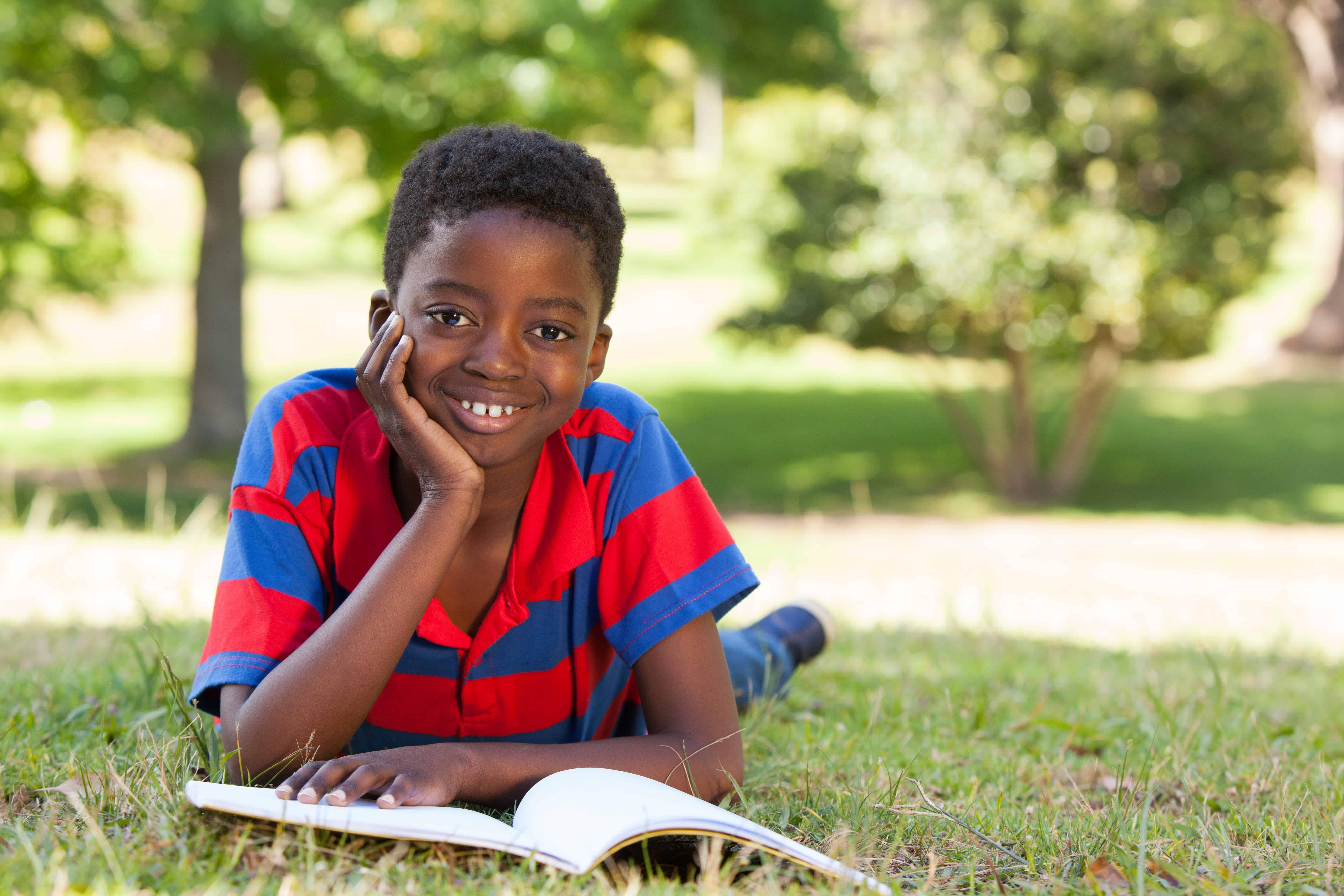 Little boy reading in the park; how to get more books to build bigger libraries