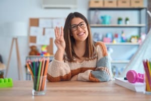 Young woman teacher wearing sweater and glasses sitting at desk at kindergarten showing and pointing up with fingers number three while smiling confident and happy. New teachers info