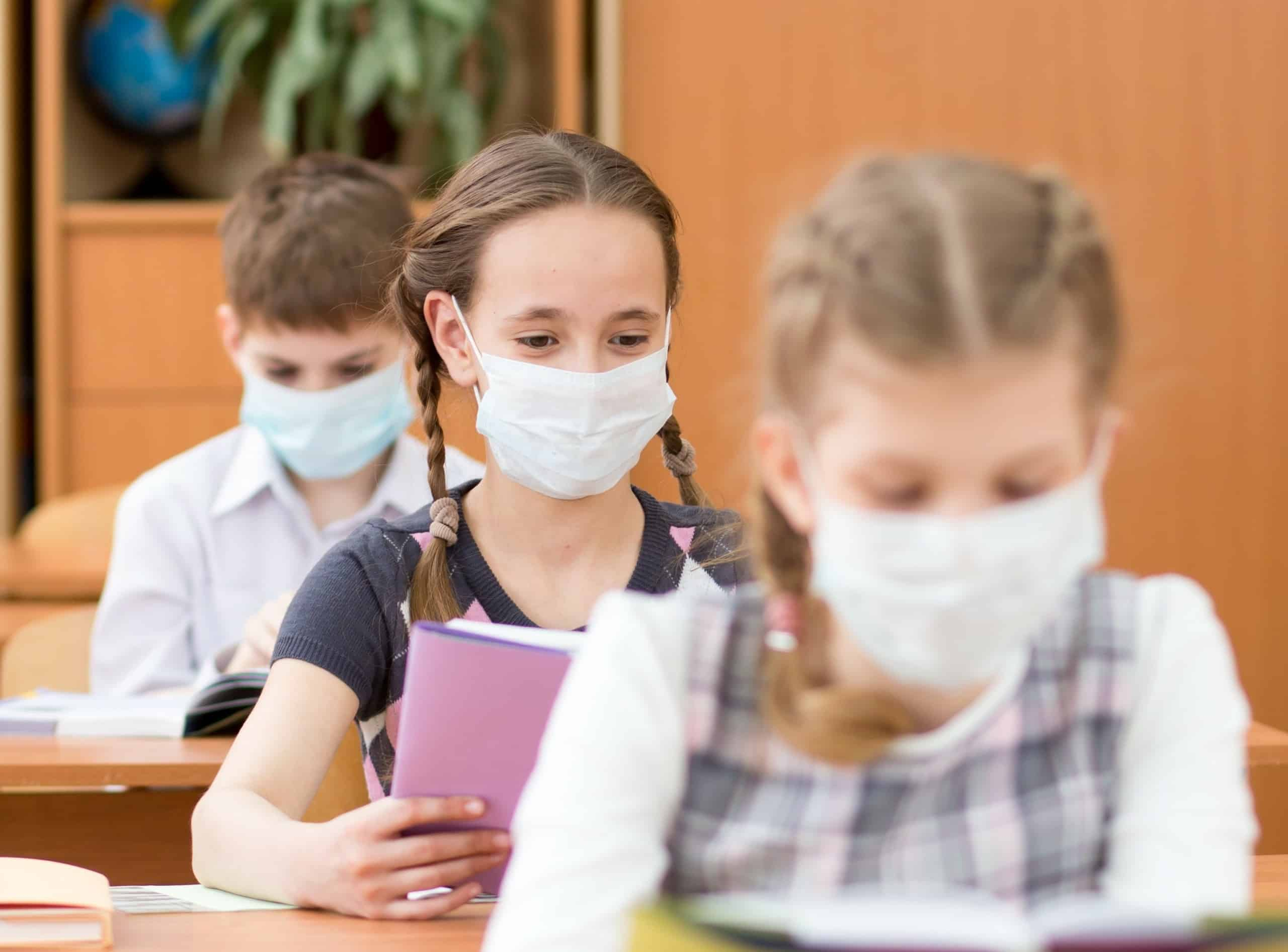 Schoolkids with medicine mask on faces against virus in classroom; keeping reading social while distancing