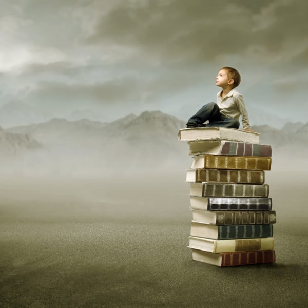 Young boy sitting atop a stack of books